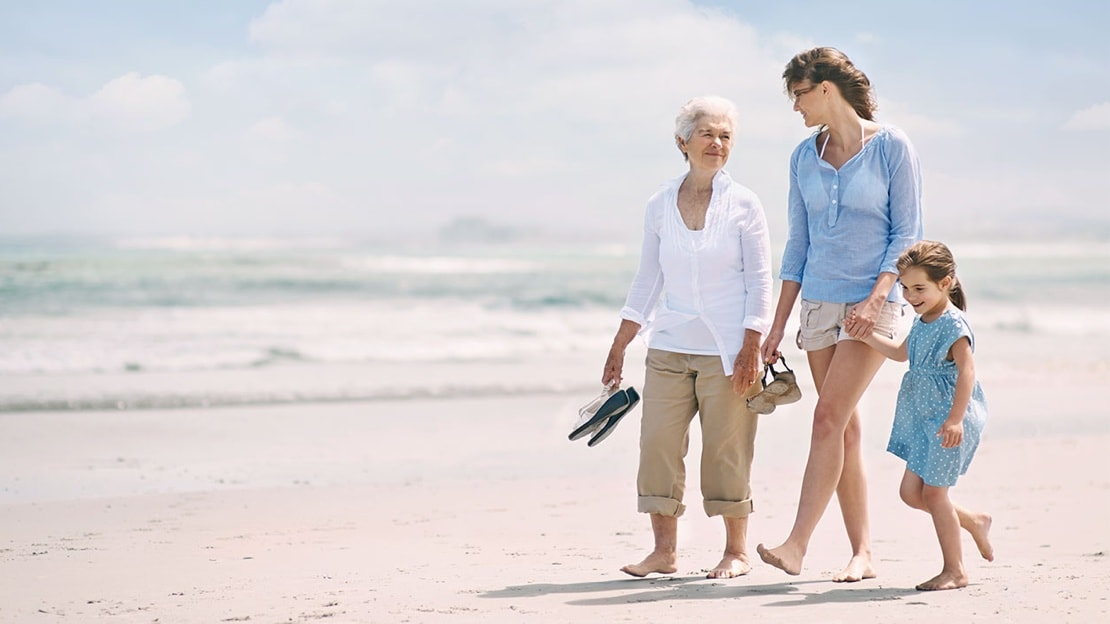 an older woman, a younger woman, and a young girl walk on the beach in the sun